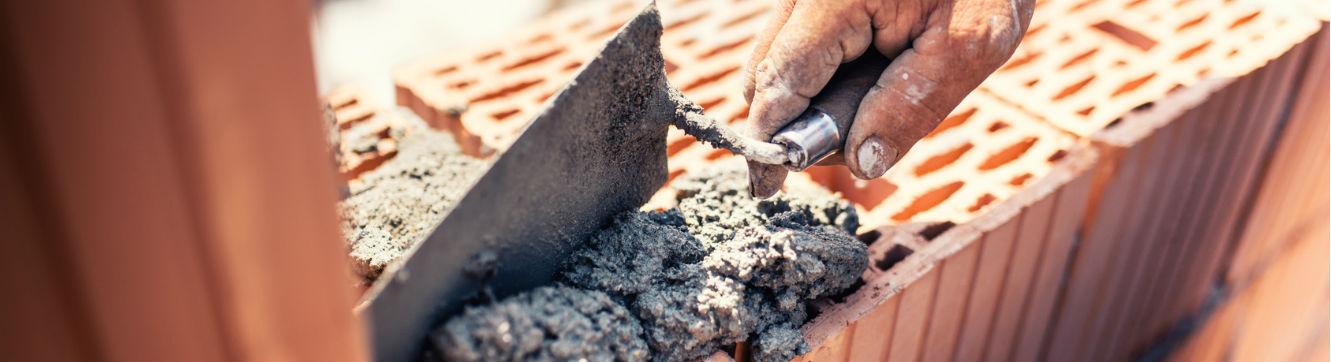 Un maçon effectue des travaux de maçonnerie