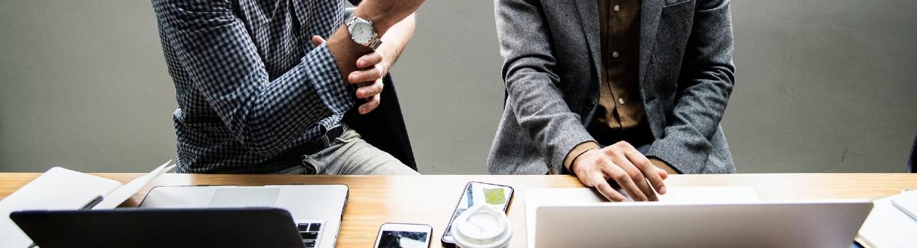 2 personnes assises autour d'une table recherchent un emploi sur leur ordinateur
