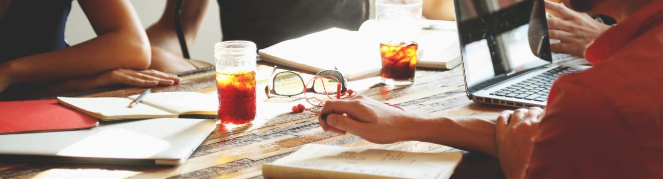 4 personnes discutent autour d'une table devant une boisson